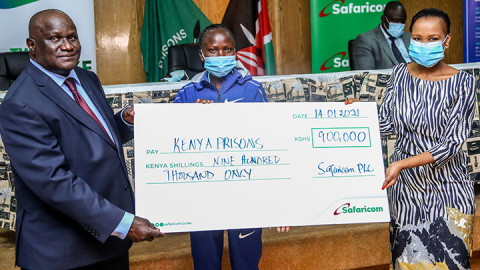 Safaricom PLC Sponsorship Manager Peris Nduta Muhoro (right) presents a dummy cheque worth Sh900,000 to World Cross Country Bronze Medallist Lilian Kasait (centre) and Commissioner General Prison Service Wycliffe Ogallo at Magereza House. PHOTO/SAFARICOM